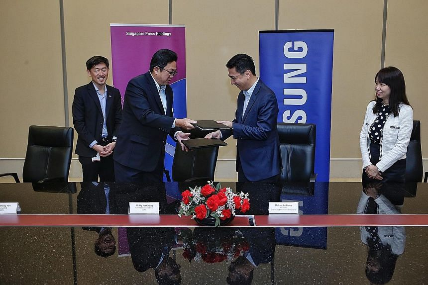 SPH chief executive Ng Yat Chung (second from left) and Samsung Electronics Singapore president Lee Jui Siang exchanging documents after signing a memorandum of understanding yesterday. With them are SPH deputy CEO Anthony Tan and Samsung Electronics