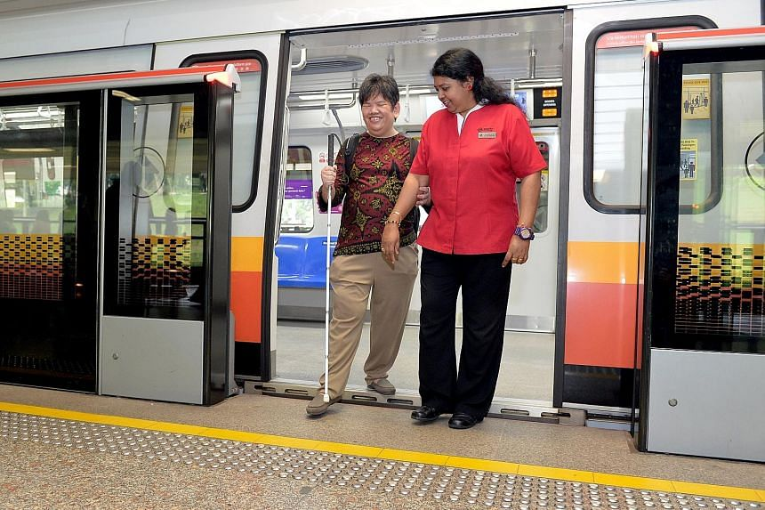 SMRT senior assistant station manager Kurinjich Chelvi assisting commuter Junaidah Ramli. SMRT said it has, since October, been training staff to understand the needs of commuters with special needs.