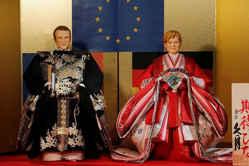 """Japanese ornamental """"hina"""" dolls made in the likeness of French President Emmanuel Macron and German Chancellor Angela Merkel were unveiled at the Kyugetsu traditional doll shop in Tokyo yesterday. The dolls were displayed ahead of Girls' Day, a holi"""