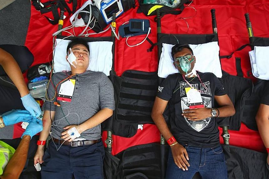"""The exercise also saw the SCDF tending to """"casualties"""" by bandaging their wounds, attaching drips and oxygen masks to them and monitoring their pulses."""