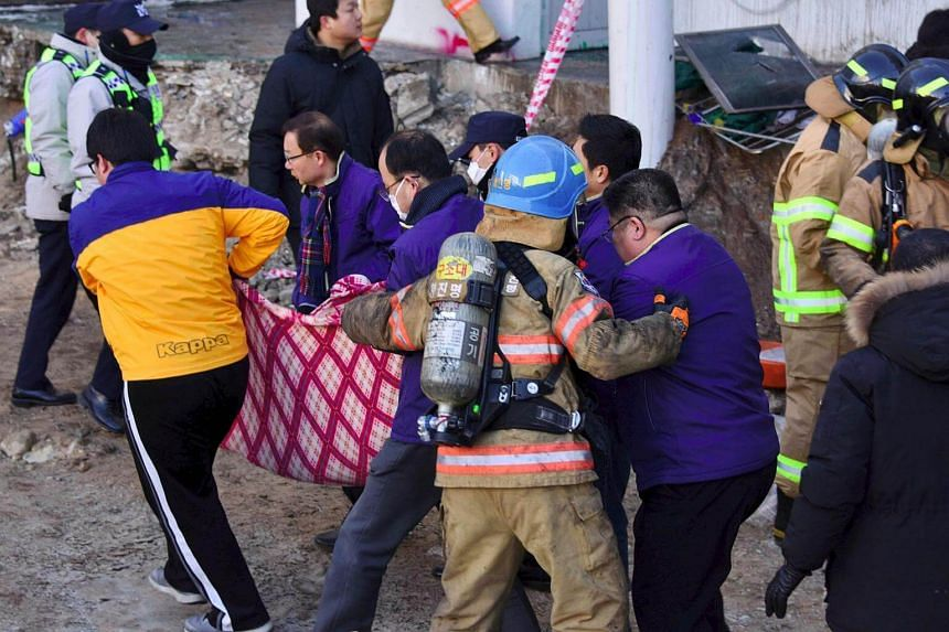 Rescue workers remove the bodies of victims after a fire at Sejong Hospital in Miryang on Jan 26, 2018.