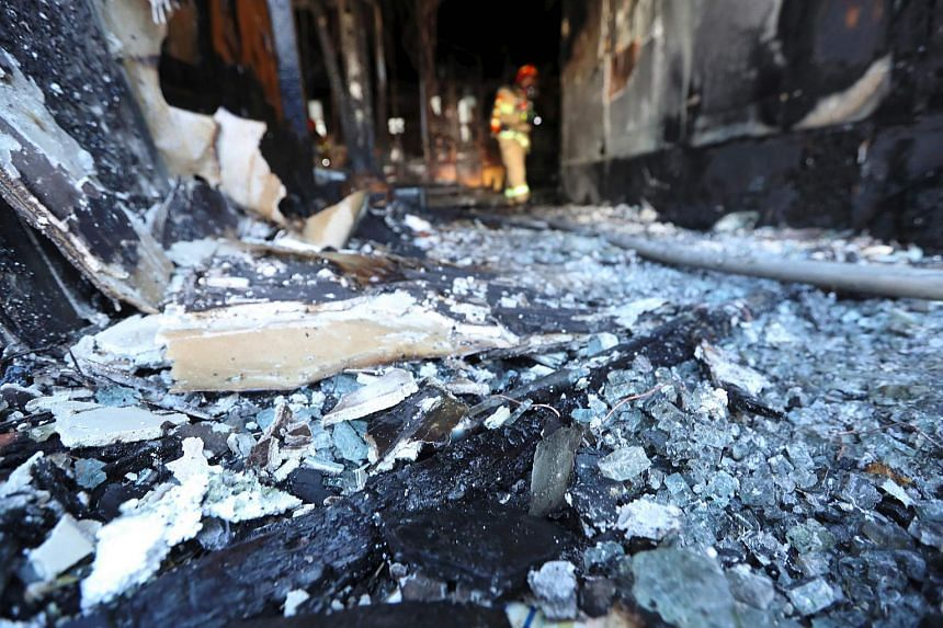 A firefighter searches the debris after the fire.