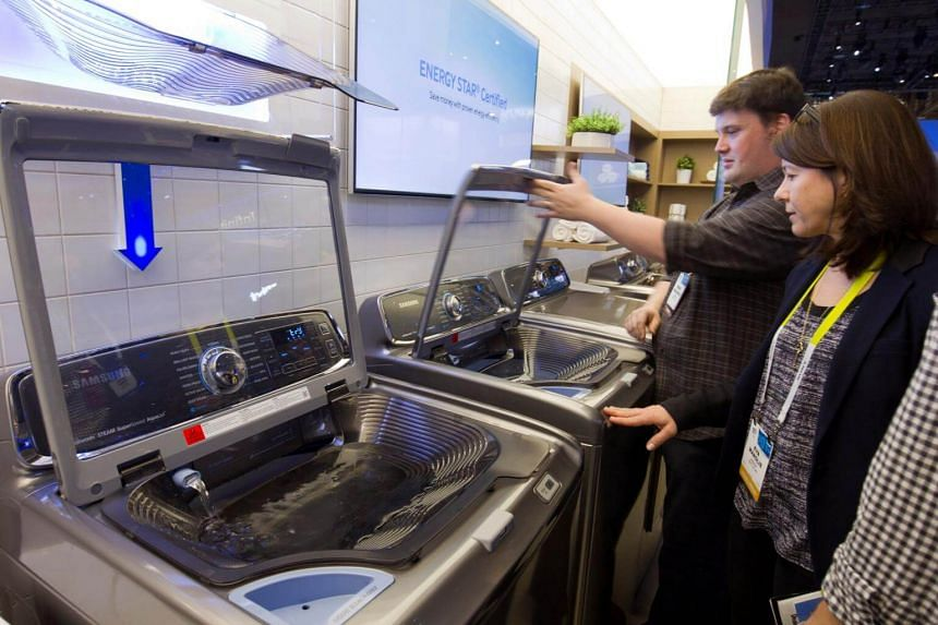"Visitors looks over an ""activewash"" Samsung washing machine with a built-in sink during the 2015 International Consumer Electronics Show (CES) in Las Vegas."