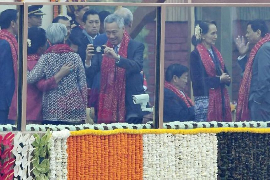 Prime Minister Lee Hsien Loong taking a photograph of his wife as Myanmar's civilian leader Aung San Suu Kyi speaks to Philippine President Rodrigo Duterte ahead of India's 69th Republic Day Parade in New Delhi on Jan 26.