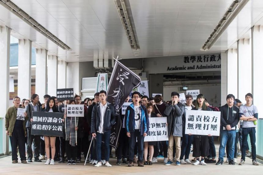 Suspended Hong Kong Baptist University students Lau Tze-kei (centre left) and Andrew Chan (centre right) lead demonstrators in a march against their suspension on Jan 26.