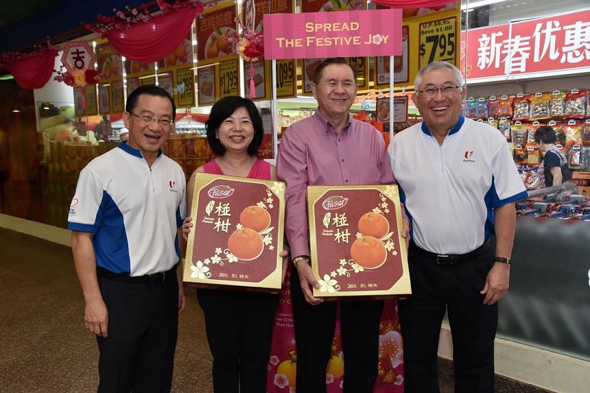 NTUC FairPrice chairman Bobby Chin (right) and chief executive Seah Kian Peng (left) presenting the first boxes of mandarin oranges to CEO of Ren Ci Hospital Ms Loh Shu Ching (second from left) and CEO of Thye Hua Kwan Moral Society Mr Lawrence Ng (s