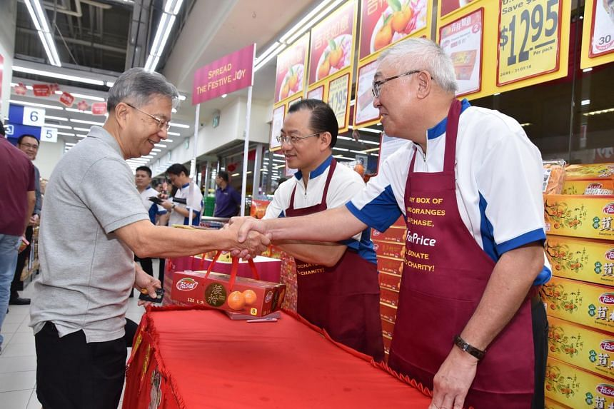 NTUC FairPrice chairman Bobby Chin (right) and chief executive Seah Kian Peng (centre) selling mandarin oranges as part of the One FairPrice Family Initiative to raise funds for Ren Ci Hospital and Thye Hua Kwan Moral Society.