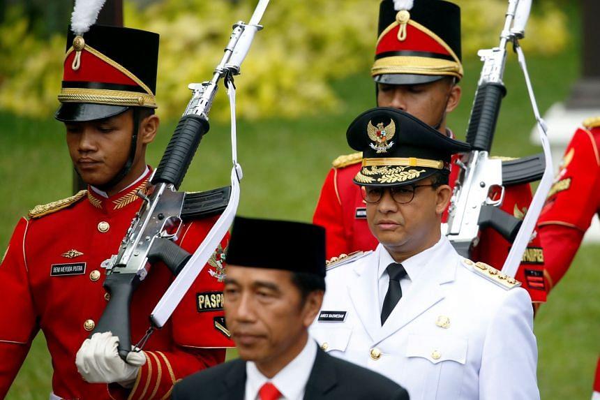 Presidential guards walk with Indonesia President Joko Widodo (left) and Jakarta Governor Anies Baswedan.