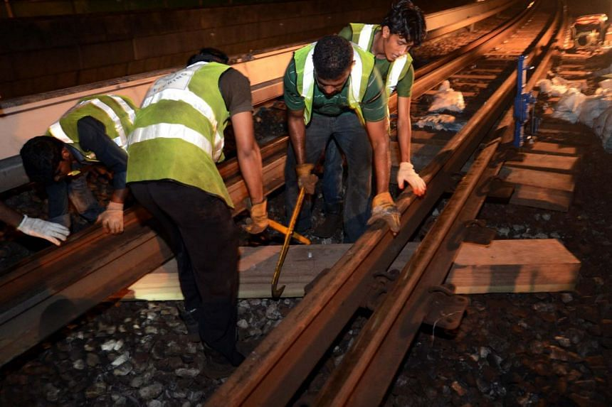 Maintenance staff replacing the wooden sleepers on the train tracks near Clementi MRT station. SMRT's director of building and facilities Sui Yow Wee said outsourcing maintenance staff allows them to fix defects across its networks faster.