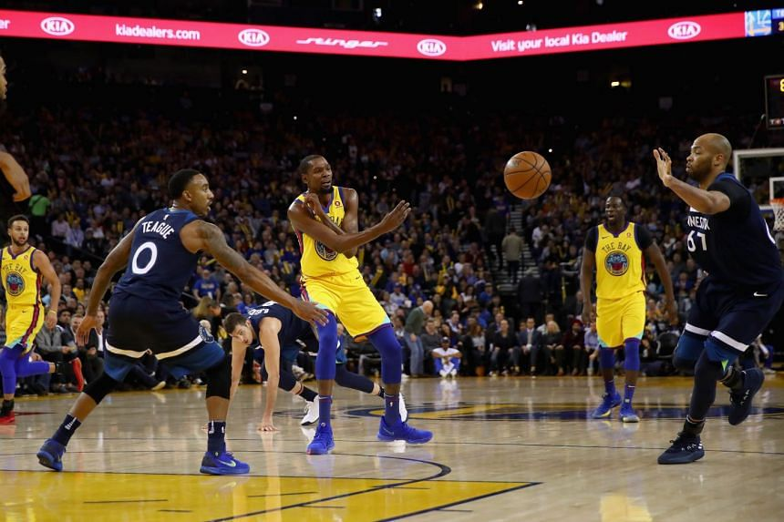 Kevin Durant passes the ball between Jeff Teagueand Taj Gibson at Oracle Arena on Jan 25, 2018 in Oakland, California.