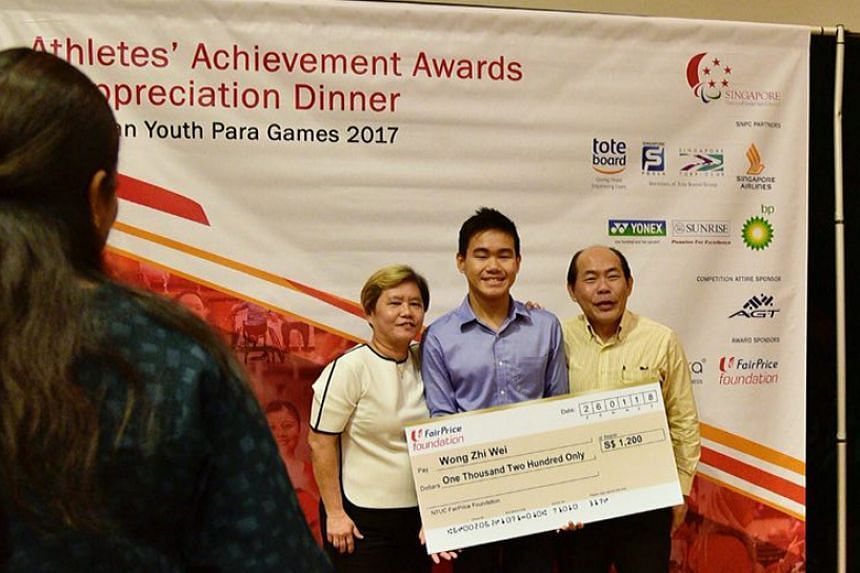 Team Singapore's Asia Youth Para Games swimmer Wong Zhi Wei, with his parents, receiving his cash award at the Athletes Achievement Awards ceremony on Jan 26.