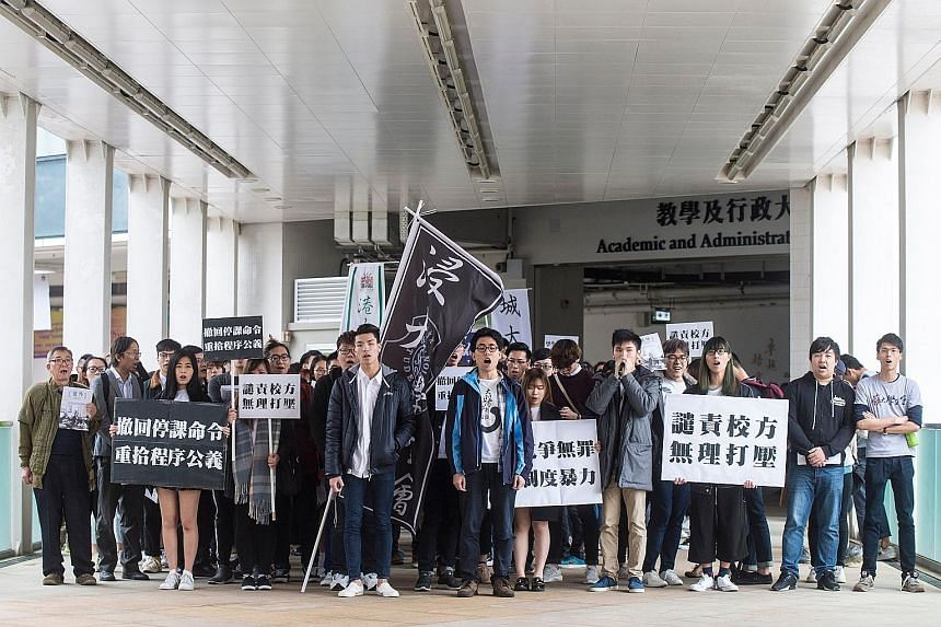 Baptist University students Lau Tsz Kei (centre, left) and Andrew Chan (centre, right) leading demonstrators yesterday in a march against their suspension from school. The duo had been suspended for confronting and swearing at staff over the requirem
