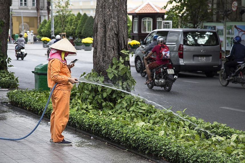 A worker in Vietnam engrossed with a smartphone while at work. The writer says that the arrival of the smartphone transformed all media and effectively put Facebook, Google, and a handful of others in control of the information flow to users.