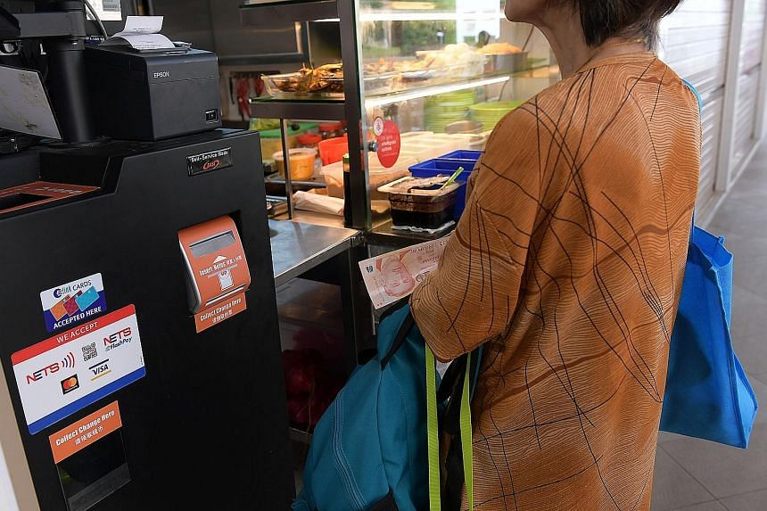 The payment kiosk at the Jurong West Street 61 hawker centre accepts both cash and cashless payments. Some hawkers say few customers opt for cashless payments.