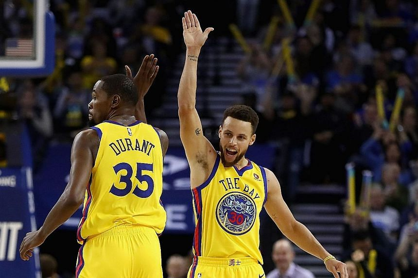 Kevin Durant and Stephen Curry exchanging high-fives on Thursday. The Warriors team-mates will be on opposing sides in the NBA All-Star game on Feb 18 as LeBron James chose Durant with his first pick.