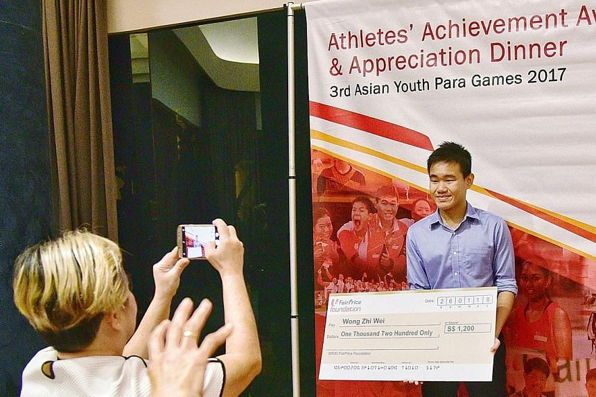 Catholic High School student Wong Zhi Wei, 15, holding a mock cheque for $1,200 while his mother Chu Lee Lee, 55, a housewife, snaps a picture at *Scape Treetop. He won three golds and two silvers in Dubai last month.