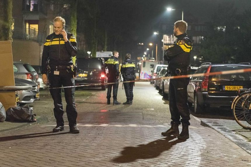 Policemen stand guard at a closed off lane in the aftermath of a shooting, at the Grote Wittenburgstraat in Amsterdam, The Netherlands, on Jan 26, 2018.