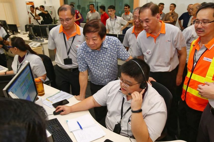 Transport Minister Khaw Boon Wan watching an assistant service controller working in the Operations Control Centre at the new Seletar Bus Depot.