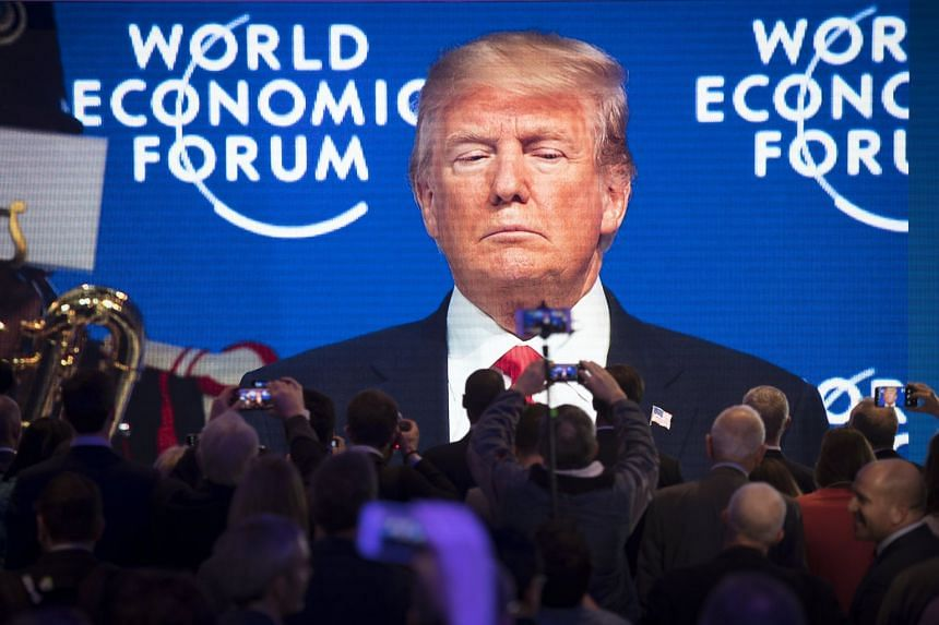 Participants watch the appearance of US President Trump on a screen from an adjacent room, during the 48th Annual Meeting of the World Economic Forum (WEF) in Davos.