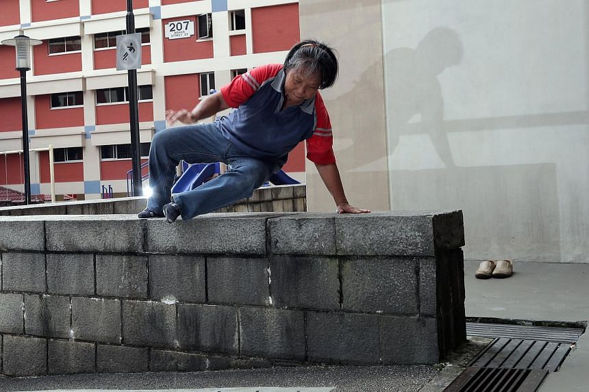 Retired graphic designer Ann Tham executing her parkour on a wall.