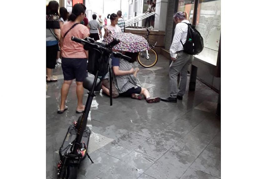 A woman was seen on the floor outside Chinatown MRT Station, with an e-scooter parked nearby.