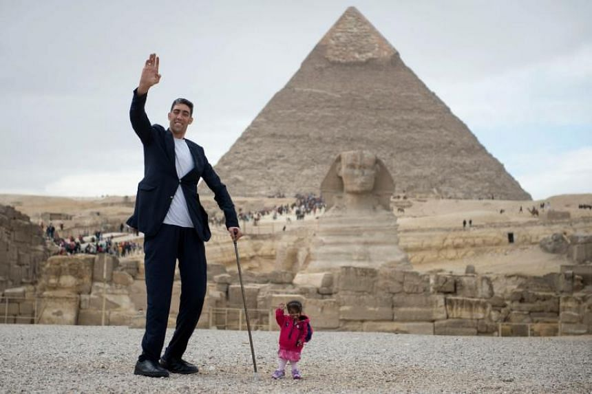 The world's tallest man, Sultan Kosen of Turkey and shortest woman, Jyoti Amge of India, pose for a photo in front of the Pyramids, in Giza, Egypt, on Jan 26, 2018.