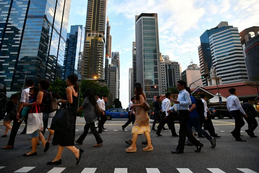 Pedestrians crossing the road along Shenton Way in Singapore's central business district.