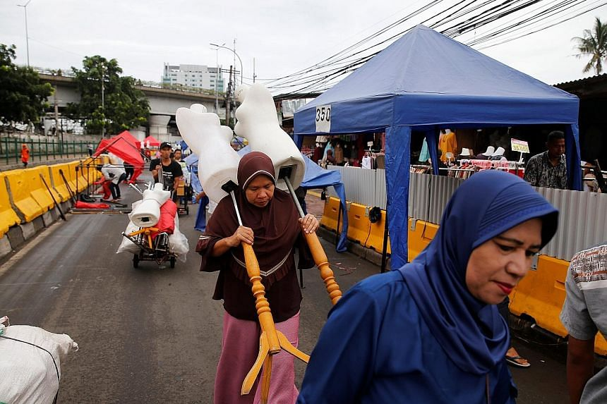 Street vendors preparing to set up their stalls in the Tanah Abang market in Jakarta. The busy area (below) in the congested Indonesian capital also has a train station and when the new governor, Anies Baswedan, closed off one of the busiest streets