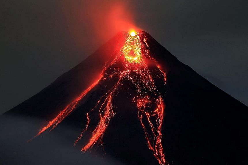 Mount Sinabung spewing thick smoke in Karo, in Indonesia's North Sumatra, on Jan 6 as a farmer harvests his vegetables. Lava flowing from the crater of Mount Mayon volcano during a new eruption in Albay province, Philippines, last Thursday. The volca