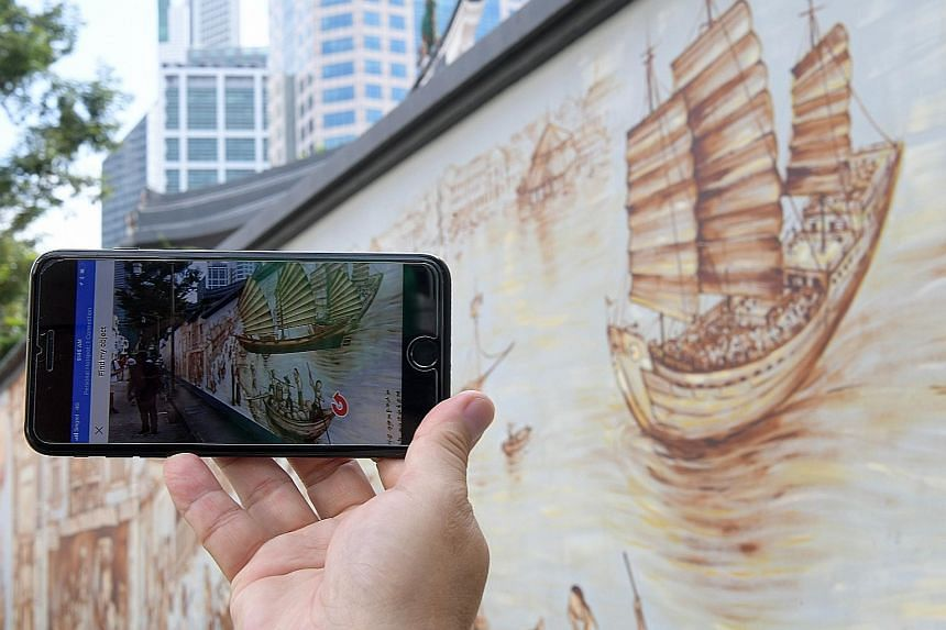 A visitor using the LocoMole app watches a junk pop off a mural behind the historic Thian Hock Keng Temple and come to life in Telok Ayer Street. Above: Cyclists stop to admire the Thian Hock Keng mural in the Telok Ayer Conservation Area. Left: Max