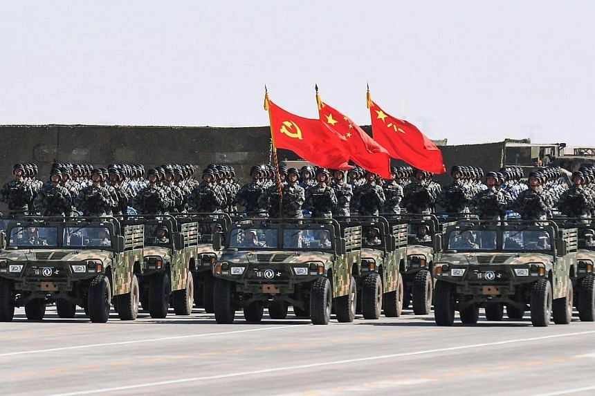 Chinese soldiers carrying the flags of (from left to right) China's Communist Party, the state, and the People's Liberation Army during a military parade at the Zhurihe training base in Inner Mongolia region on July 30, 2017.