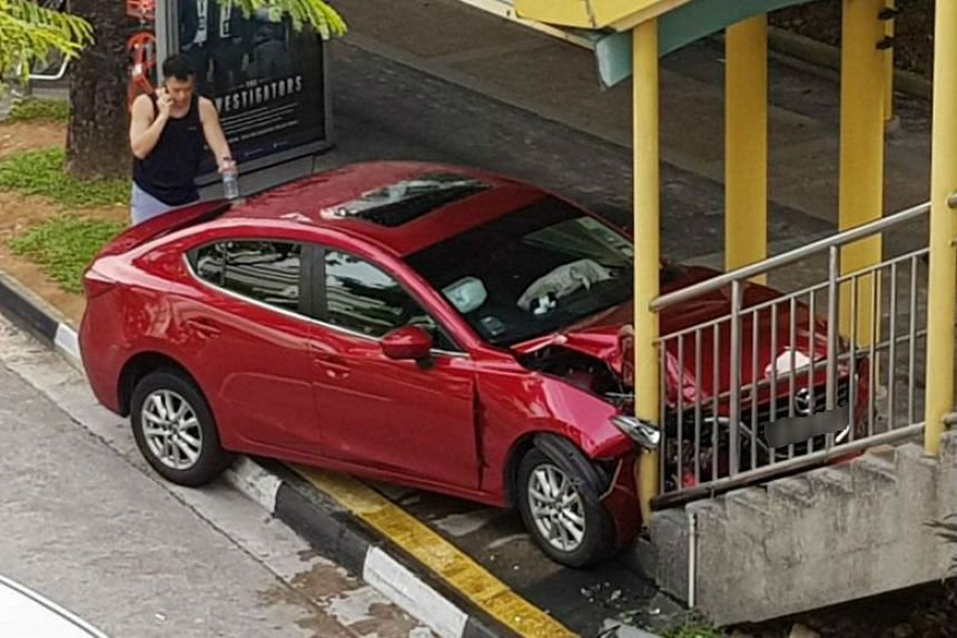 The red Mazda appeared to be heavily damaged after hitting the railing at the base of the bridge's staircase in Jurong East Central on Jan 26, 2018.