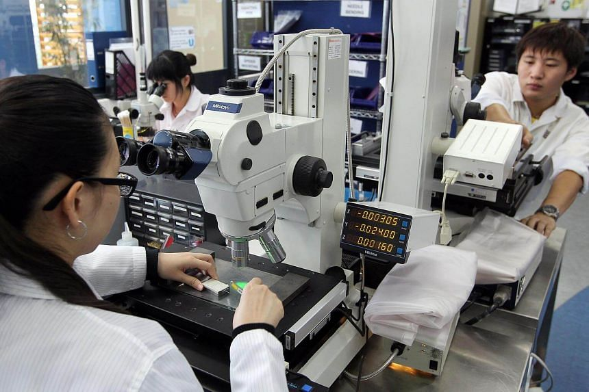 Staff of precision-engineering firm Feinmetall Singapore at work. The company received cash help from the Productivity and Innovation Credit scheme to upgrade software, train staff and purchase new equipment.