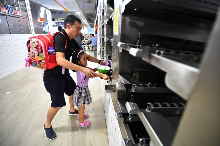 Mr Vincent Teo returning a tray to the tray return station with his daughter Alecia at the Bukit Merah Central food centre.