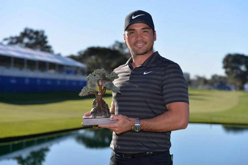 Jason Day poses for a photograph with the winner's trophy following the playoff round of the Farmers Insurance Open golf tournament at Torrey Pines Municipal Golf Course.