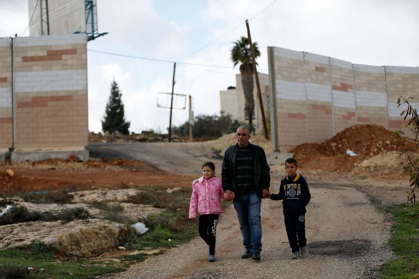 Members of the Palestinian Jumaa family, whose house became encircled by Israel's controversial separation barrier, north of Ramallah.