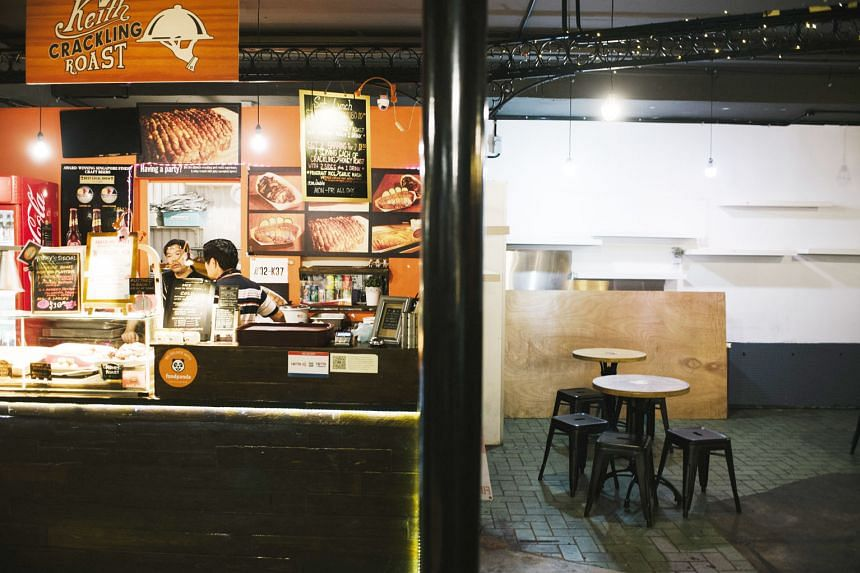 A food stall still in operation is adjacent to an already-shuttered outlet at PasarBella. The area once occupied by the closed outlet has been converted into extra seating space for customers.