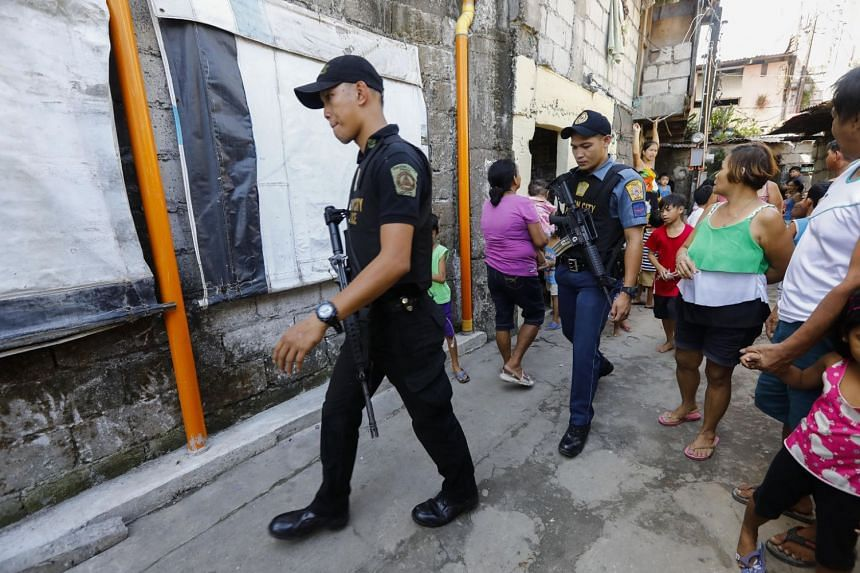 Philippine police walk through an alley of a local community where an anti-illegal drugs campaign is conducted in Quezon City, east of Manila, Philippines, on Jan 29, 2018.