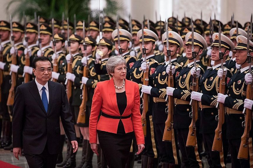 Chinese Premier Li Keqiang and British Prime Minister Theresa May inspecting the ceremonial guard at the Great Hall of the People in Beijing yesterday.