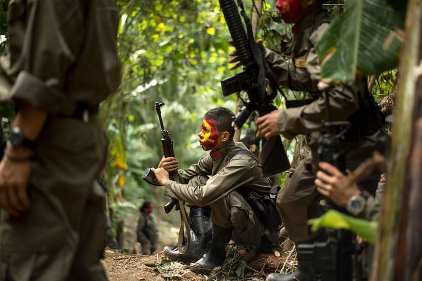 Guerrillas of the New People's Army resting amongst the bushes in the Sierra Madre mountain range, located east of Manila on July 30, 2017.