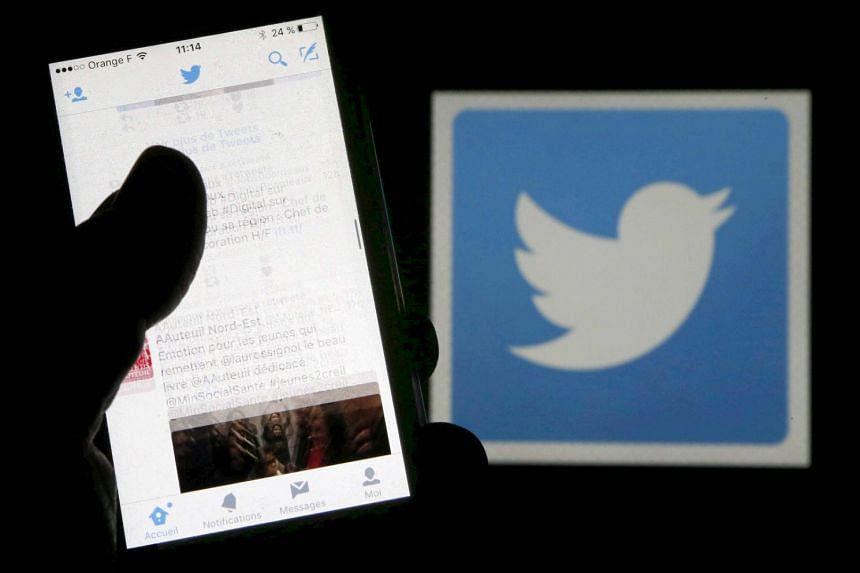 A man reads tweets on his phone in front of a displayed Twitter logo in Bordeaux, southwestern France.
