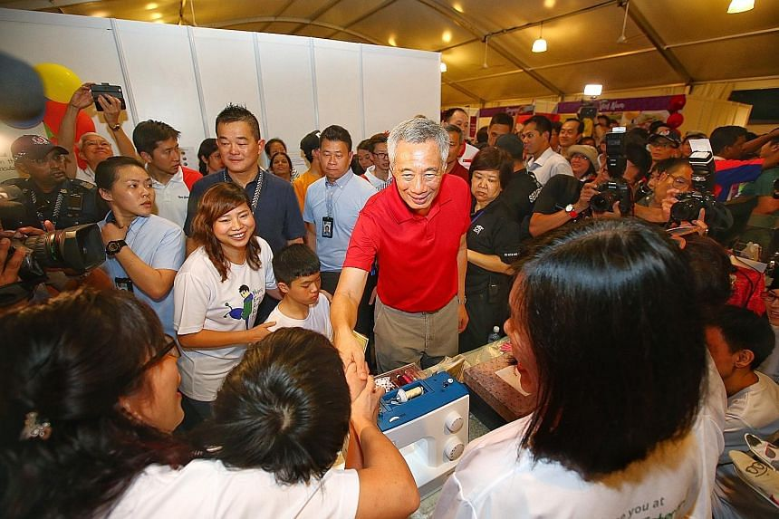 Prime Minister Lee Hsien Loong visiting a booth at the Experience Asean festival at Bishan-Ang Mo Kio Park last month. PM Lee, who has said he hopes not to stay on as PM beyond age 70, has about four years to hand over the post. But having him stay o
