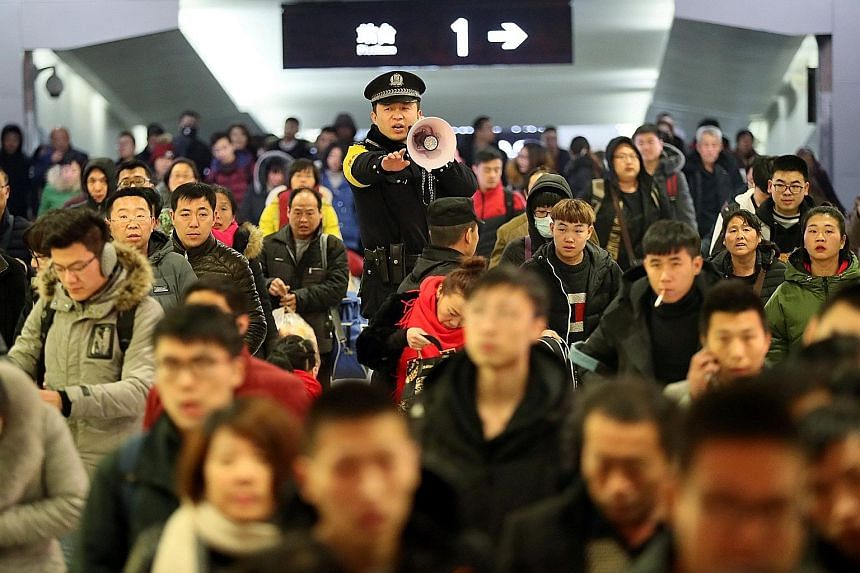 A policeman keeping order at a train station as the travel rush begins. Some stations have started using facial recognition technology to facilitate check-in.
