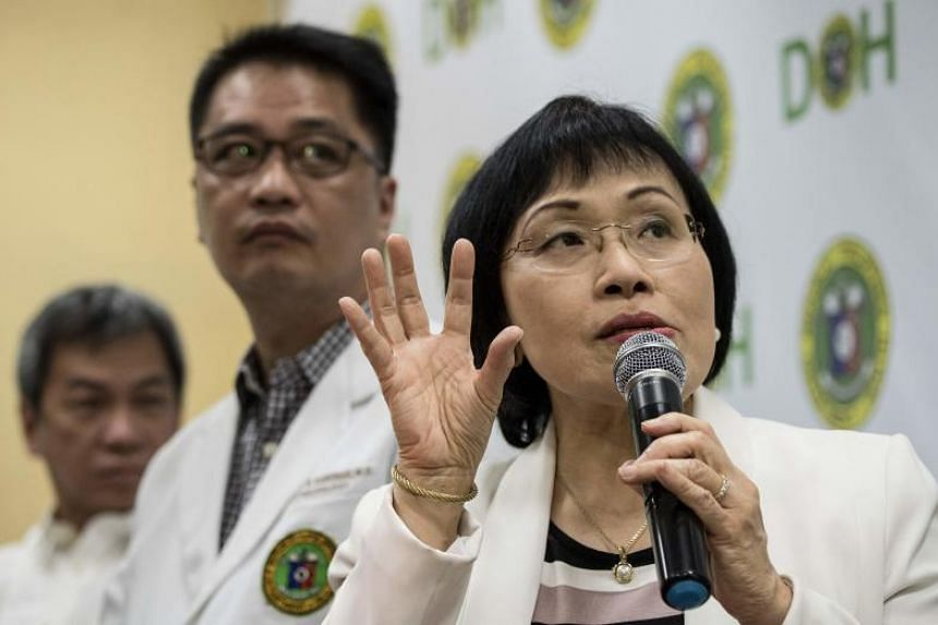 Juliet Sio-Aguilar, pediatrician and head of the Philippine General Hospital expert panel, speaks during a press conference regarding the Dengvaxia vaccine on Feb 2, 2018, while Health Under-secretary Enrique Domingo (centre) looks on.
