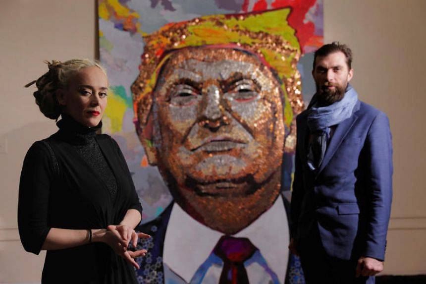 Artists Daria Marchenko and Daniel D. Green stand in front of their portrait of US President Donald Trump, which is made of coins and casino tokens, in a classroom in New York, US on Jan 31, 2018.