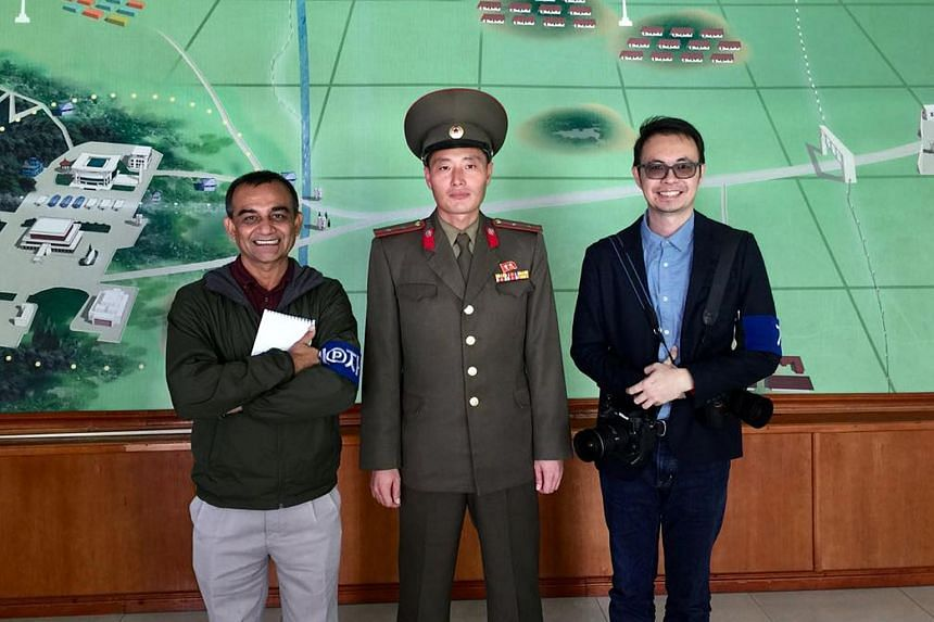 The Straits Times' associate editor Rahul Pathak (left) and executive photojournalist Desmond Foo flanking a North Korean officer at the Demilitarized Zone - described as the most dangerous place in the world - on the border of the two Koreas.