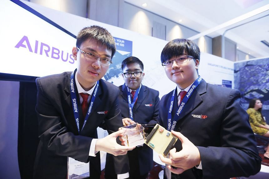 Singapore Polytechnic engineering students (from left) Pan Ziyue, Goh Qian Zhe and Julian Kang with a prototype cube satellite that they developed at the Global Space and Technology Convention at Sheraton Towers yesterday. The trio, who have their ow