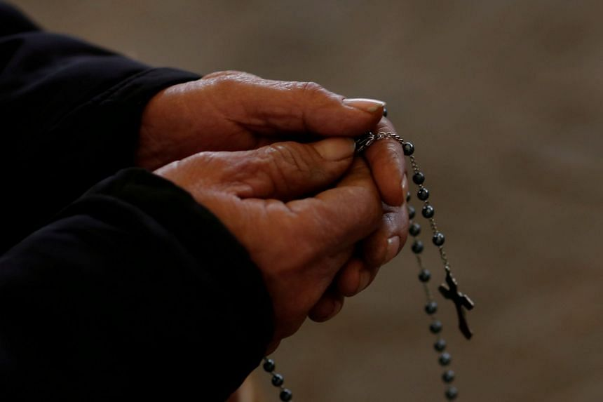 A man holds a rosary during Sunday service at a makeshift, tin-roofed church in Youtong village, Hebei Province, China. Under the formal deal, the Vatican will have a say in negotiations for the appointment of future bishops.