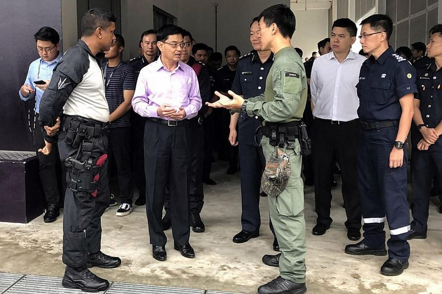 Finance Minister Heng Swee Keat being briefed by officers from the Singapore Police Force and Singapore Civil Defence Force during a visit to the Home Team Tactical Centre yesterday.