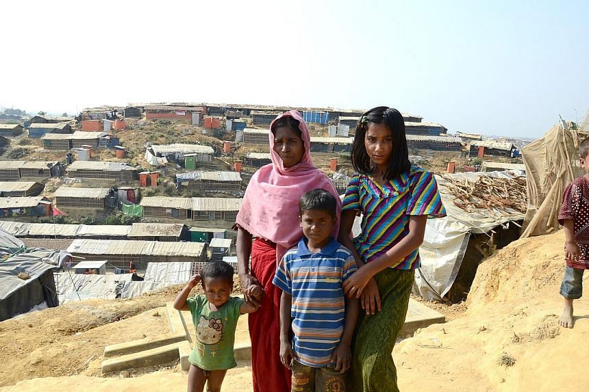 The hills in southern Cox's Bazar have been stripped of foliage and packed instead with thousands of bamboo-framed, tarpaulin-lined huts. Left: Ms Khursida Begum, 20, a Rohingya refugee with two children. She is one of the female volunteers engaged b